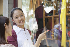 Compra da janela de duas jovens mulheres Foto de Stock Royalty Free