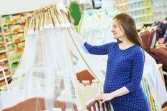 Compra da jovem mulher durante a gravidez foto de stock