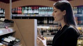 Compra da jovem mulher no supermercado Pensando o que deve comprar em seguida, andando com o trole perto da loja de vinho imagens de stock royalty free