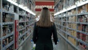 Compra da jovem mulher no supermercado Pensando o que deve comprar em seguida, andando com o trole perto da loja de vinho filme