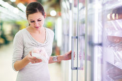 Compra da jovem mulher para a carne em uma mercearia Imagens de Stock