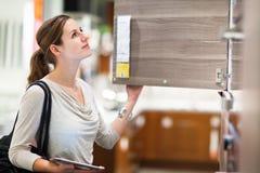 Compra da jovem mulher para a mobília em uma loja de móveis Imagem de Stock Royalty Free