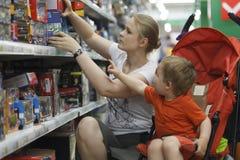 Compra da mãe e do filho para brinquedos Fotografia de Stock Royalty Free