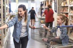 Compra da m?e e da filha no supermercado que escolhe produtos imagem de stock