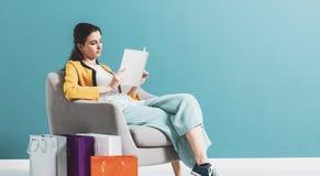 Compra da mulher e leitura de um compartimento de forma imagens de stock