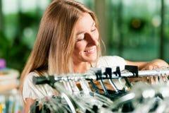 Compra da mulher em uma loja de roupa fotos de stock royalty free