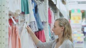 Compra da mulher em uma loja de roupa para crianças roupa do ` s das crianças em ganchos video estoque