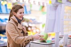 Compra da mulher nova para frutas e verdura Fotos de Stock