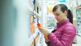 Compra da mulher para o detergente em um supermercado vídeos de arquivo