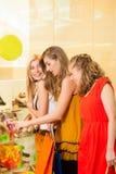 Compra da sapata dos amigos em uma alameda Fotos de Stock Royalty Free