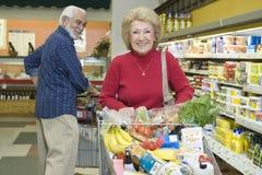 Compra de alimento superior dos pares no supermercado imagens de stock