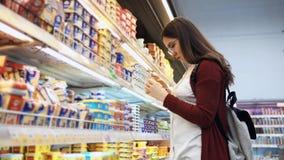 Compra de la mujer joven el queso en el supermercado almacen de metraje de vídeo