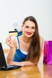 Compra de la mujer joven en el Internet Foto de archivo