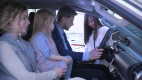 Compra de los vehículos de la familia, pareja joven con la muchacha linda del niño que habla del automóvil de compra con la mujer almacen de video