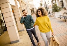 Compra de sorriso nova dos pares em uma rua urbana fotografia de stock