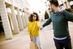 Compra de sorriso nova dos pares em uma rua urbana fotografia de stock royalty free