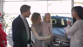 A compra do carro de família, pais felizes do cliente com filha pequena consulta com a vendedora na compra do automóvel em vendas video estoque