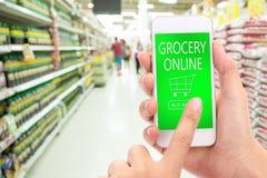 COMPRA do clique da mão da mulher AGORA no móbil com o backgro do supermercado do borrão Foto de Stock Royalty Free