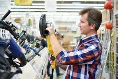 Compra do homem para o moedor de ângulo na loja de ferragens Imagens de Stock