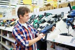 Compra do homem para o perfurador na loja de ferragens Imagem de Stock