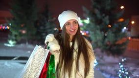 Compra do Natal do conceito - mulher bonita com pacotes multi-coloridos nas mãos que anda na noite no Natal de passeio vídeos de arquivo