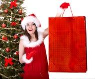 Compra do Natal da menina no chapéu de Santa, árvore de abeto. Fotografia de Stock Royalty Free