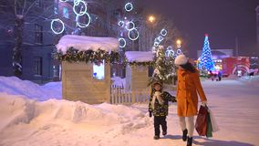 Compra do Natal, idéia para seu projeto Xmas Clientes do feriado do Natal na noite, na rua ocupada transversal da cidade, na mãe  vídeos de arquivo