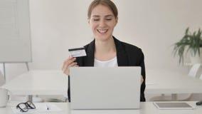 Compra em linha bem sucedida pela mulher de negócios nova no portátil video estoque