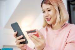 Compra em linha da mulher asiática com cartão e telefone celular de crédito em casa estilo de vida digital com tecnologia imagem de stock