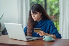 Compra em linha da mulher asiática usando o cartão de crédito com comput do portátil Fotos de Stock