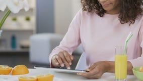 Compra em linha, desdobramento da mulher da raça consideravelmente misturada na tabuleta na cozinha vídeos de arquivo