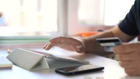 Compra em linha do Internet Um homem incorpora a informação do cartão de crédito no Web site de uma loja em linha video estoque