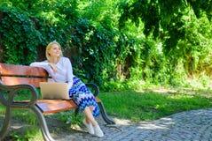 Compra em linha A menina senta o banco com caderno A mulher com o portátil no parque aprecia a natureza verde e o ar fresco Menin foto de stock royalty free