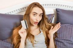 Compra emocional da mulher do sorriso no cart?o de banco da terra arrendada do Internet e na ela que encontram-se na cama em casa imagem de stock royalty free