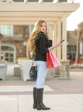 Compra fêmea loura nova com os sacos cor-de-rosa e vermelhos que guardam um telefone celular imagem de stock royalty free