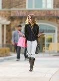 Compra fêmea loura nova com os sacos cor-de-rosa e vermelhos que guardam um telefone celular imagens de stock