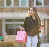 Compra fêmea loura nova com os sacos cor-de-rosa e vermelhos que guardam um telefone celular fotografia de stock royalty free