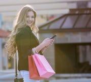 Compra fêmea loura nova com os sacos cor-de-rosa e vermelhos que guardam um telefone celular imagens de stock royalty free