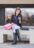 Compra fêmea loura nova com os sacos cor-de-rosa e vermelhos que guardam um telefone celular fotografia de stock