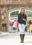 Compra fêmea loura nova com os sacos cor-de-rosa e vermelhos que guardam um telefone celular foto de stock royalty free