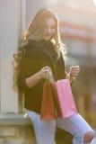 Compra fêmea loura nova com os sacos cor-de-rosa e vermelhos que guardam um telefone celular fotos de stock