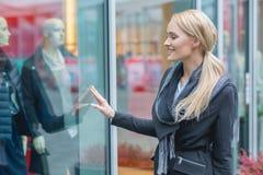 Compra feliz da janela da jovem mulher Fotos de Stock