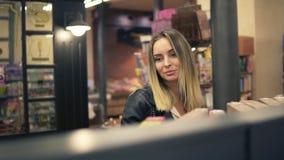 Compra feliz da jovem mulher na mercearia Mulher ocasional que escolhe o alimento da prateleira no supermercado Cliente de sorris filme