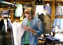 Compra feliz do homem para a roupa na loja de roupa Fotografia de Stock Royalty Free