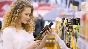 Compra na loja A jovem mulher escolhe o alimento no mercado filme