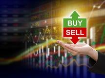 Compra o venta de la tenencia de la mano de la mujer de negocios Imágenes de archivo libres de regalías