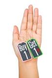A compra 1 obtém 1 etiqueta da etiqueta na mão das mulheres isolada no fundo branco Fotografia de Stock Royalty Free