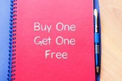 A compra uma obtém um livre escreve no caderno Fotografia de Stock Royalty Free