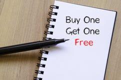 A compra uma obtém um livre escreve no caderno Imagens de Stock Royalty Free