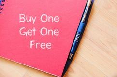 A compra uma obtém um livre escreve no caderno Foto de Stock